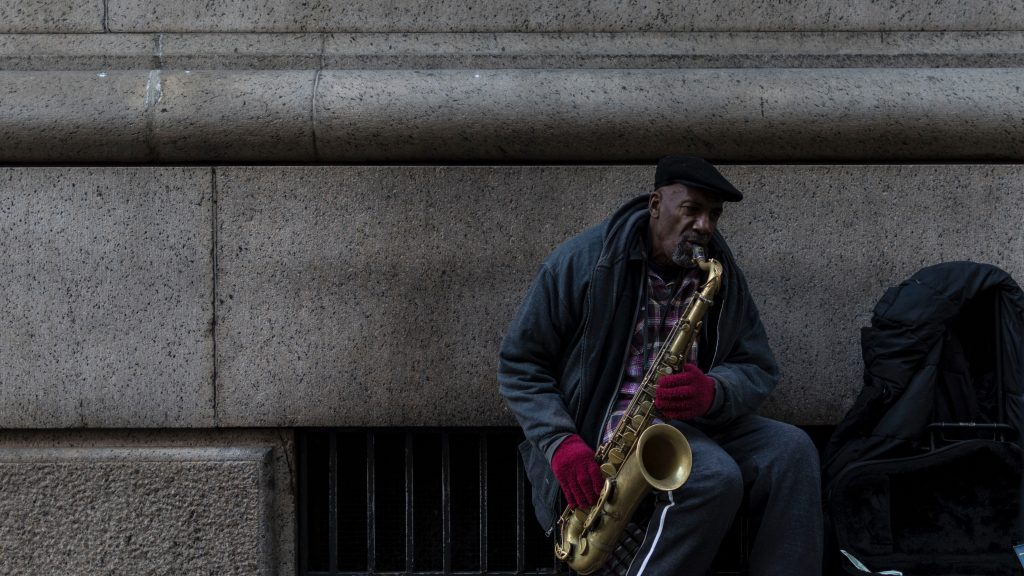 A saxophonist busking ( Photo by Marcello Vercesi on Unsplash)