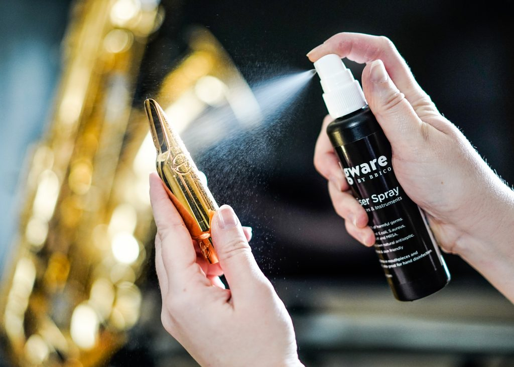 Cleaning a metal saxophone woodwind mouthpiece with Edgware Sanitiser Spray