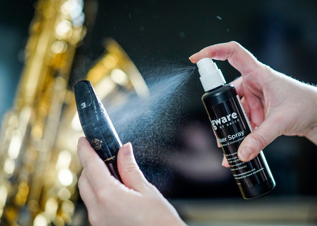 Cleaning an ebonite saxophone woodwind mouthpiece with Edgware Sanitiser Spray